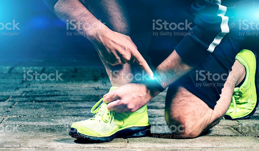Runner adjusts his wearable fitness tracker before run stock photo
