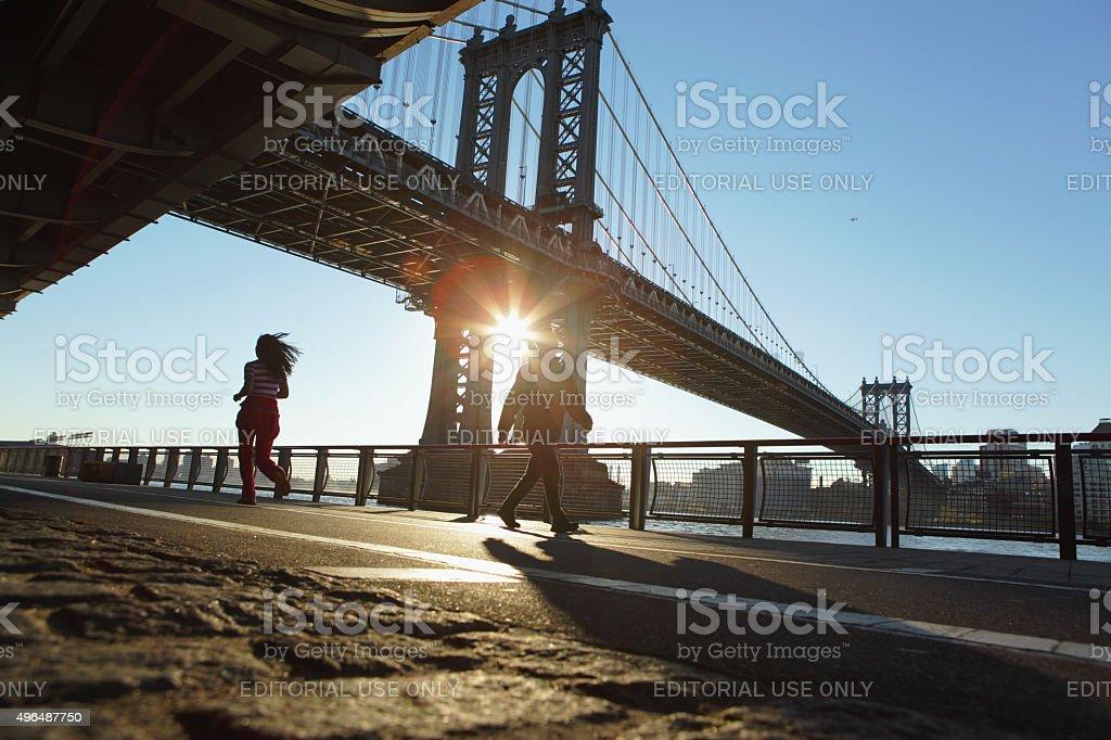 Runner and walker at sunrise under the Manhattan Bridge NYC stock photo
