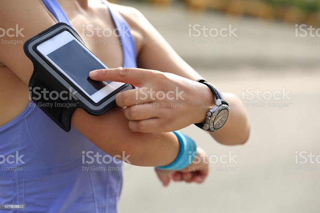 Runner athlete listening to music from smart phone mp3 player stock photo