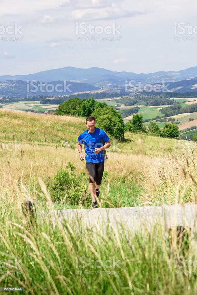 Runner athlete running on road at mountains background stock photo