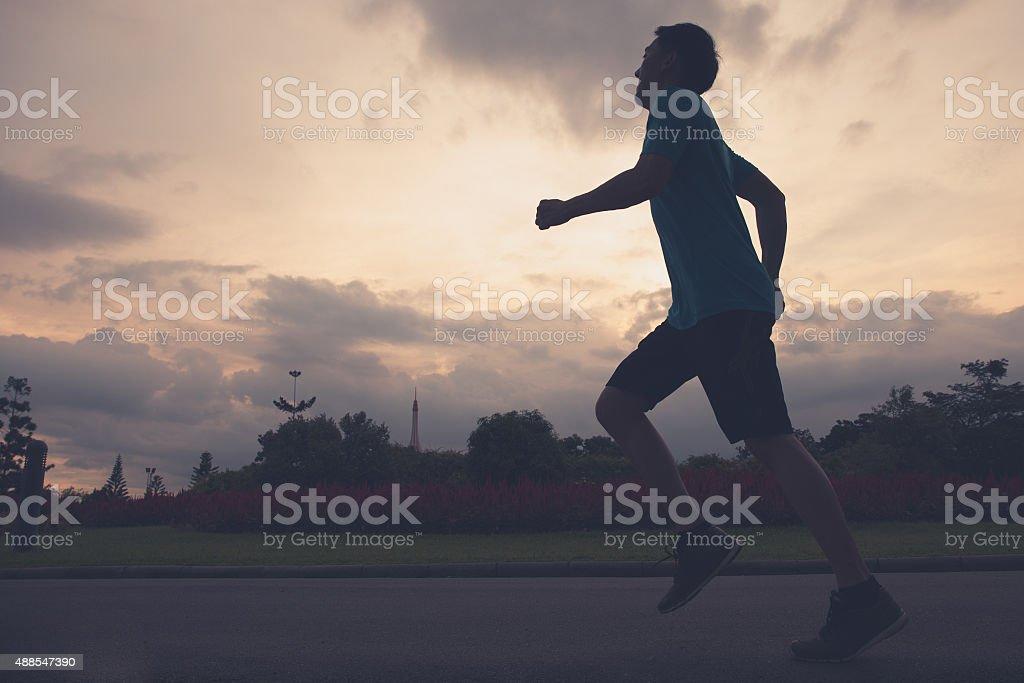 Runner athlete silhouette running in public park stock photo