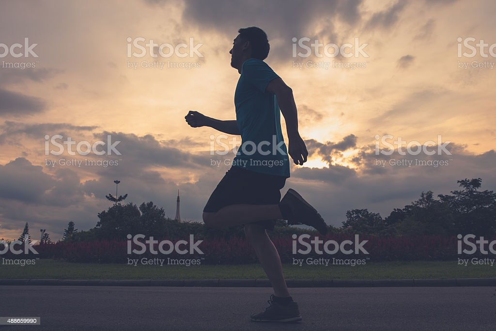 Runner athlete silhouette running in public park stock photo