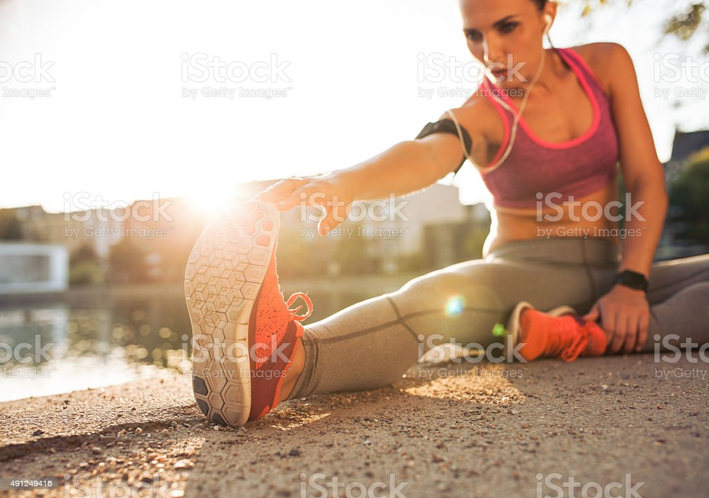 Runner athlete stretching legs stock photo