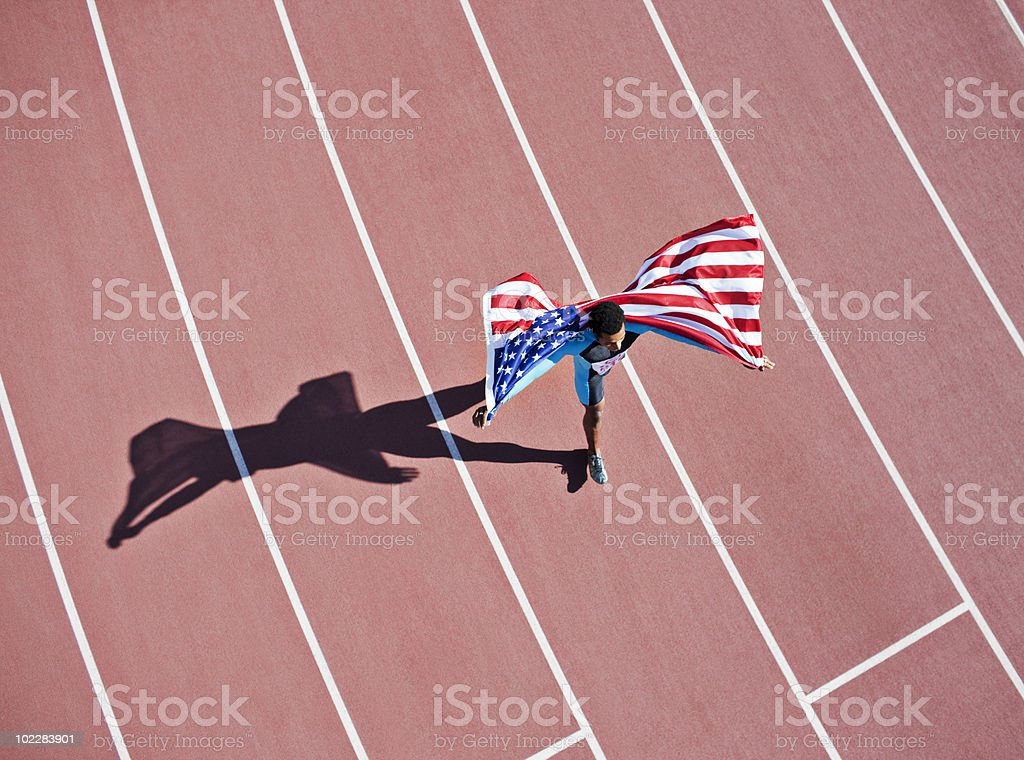 Runner celebrating on track with American flag stock photo