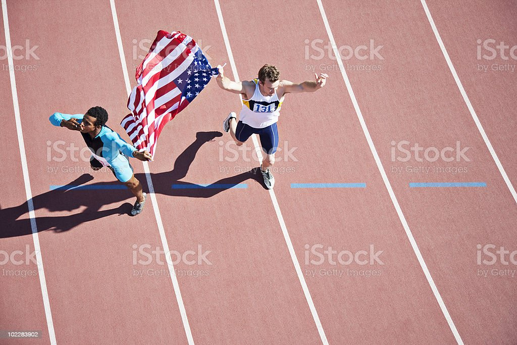 Runner celebrating on track with American flag royalty-free stock photo