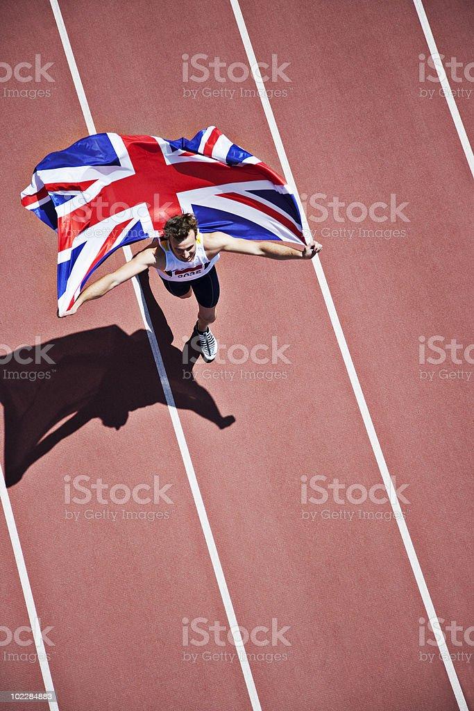 Runner celebrating with British flag on track stock photo