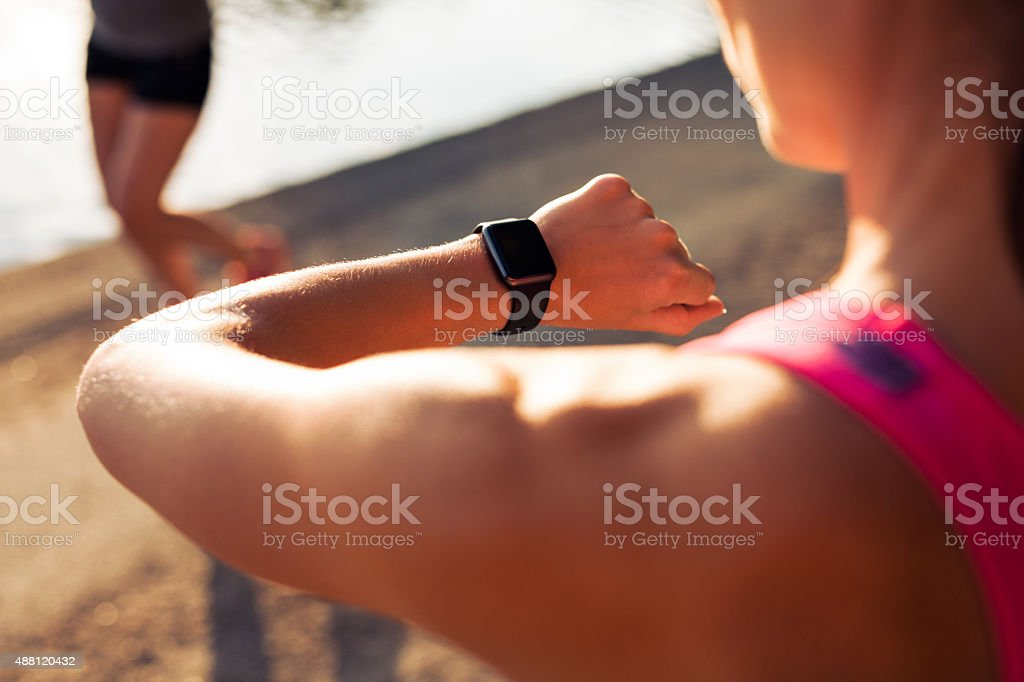 Runner checking time on her smartwatch stock photo