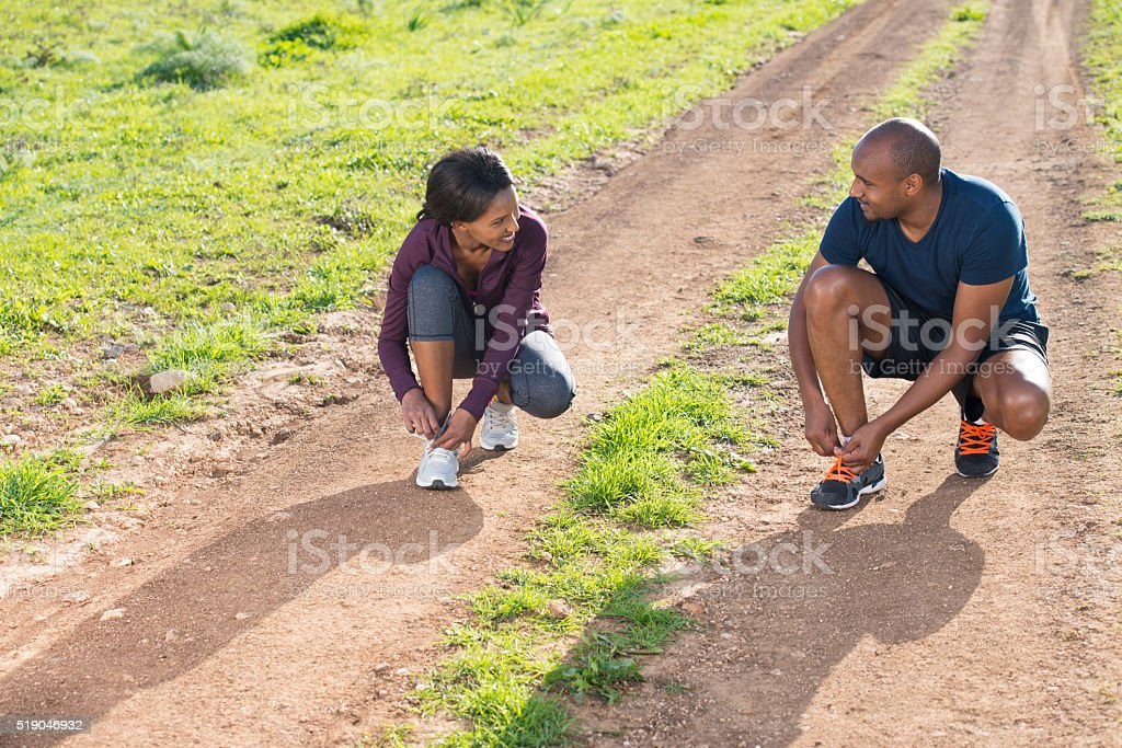 Runner couple tying sport shoes. stock photo