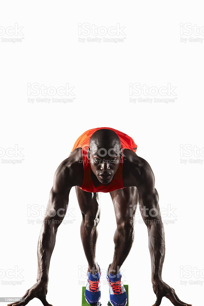 Runner crouched at starting line stock photo
