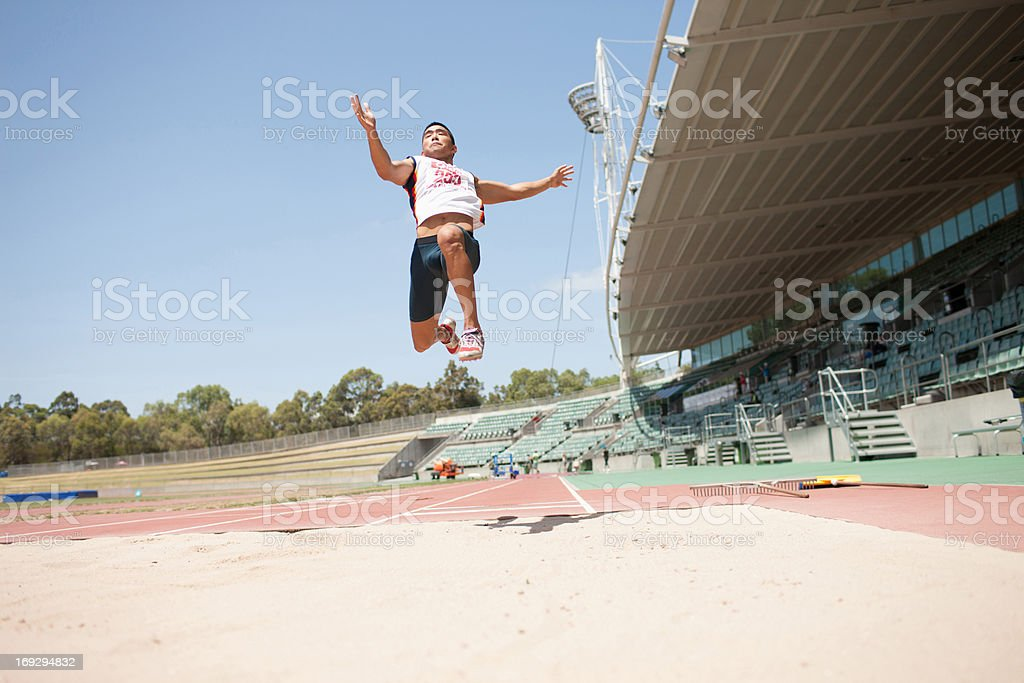 Runner doing long jump stock photo