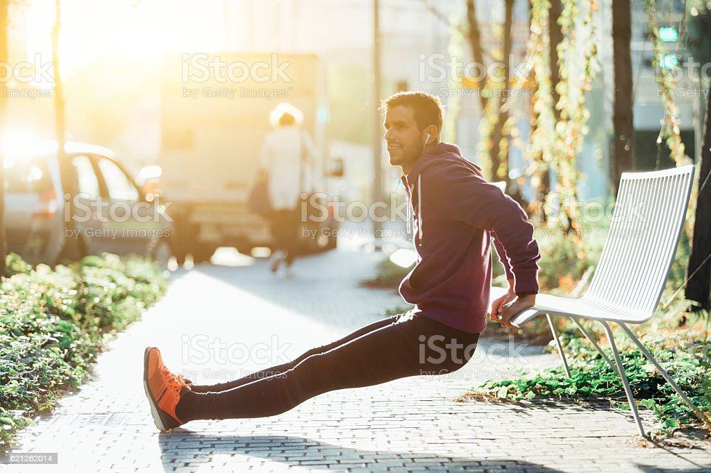 runner doing some tricep dips on a bench stock photo