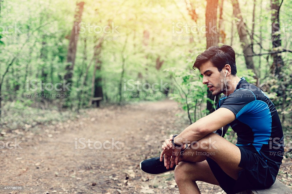 Runner in the park sitting at bench stock photo