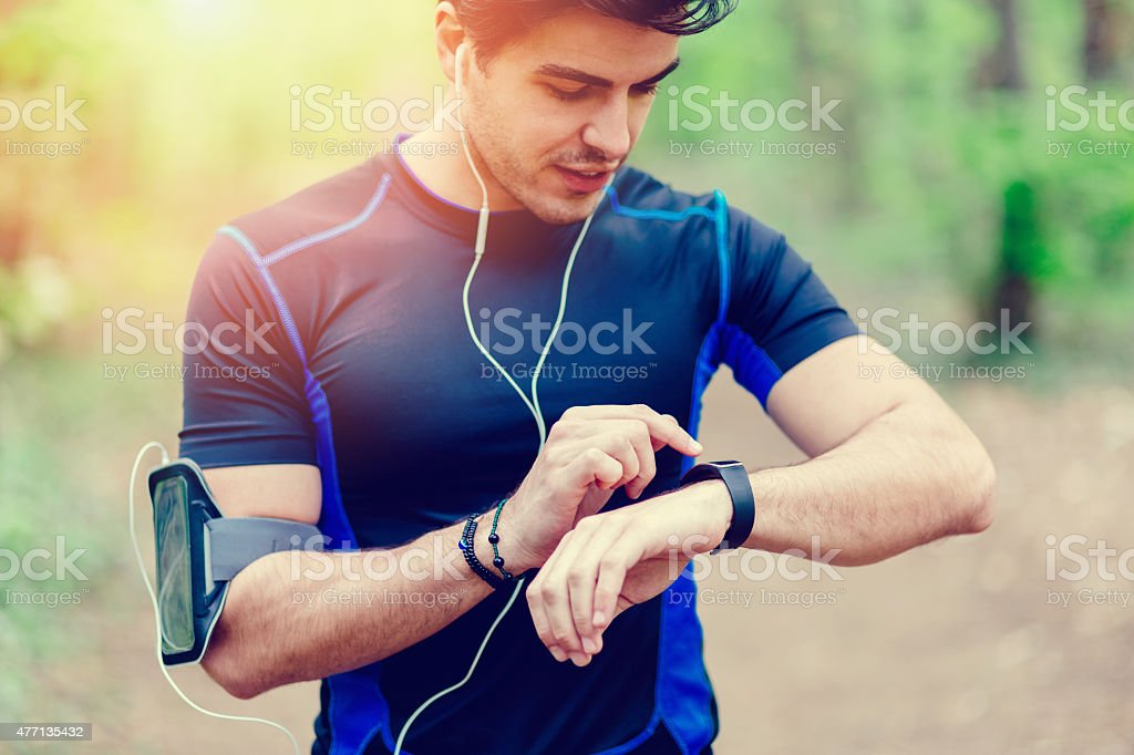 Runner in the park using smart watch stock photo