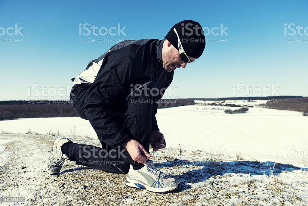 Runner in winter landscape is tying a shoe royalty-free stock photo