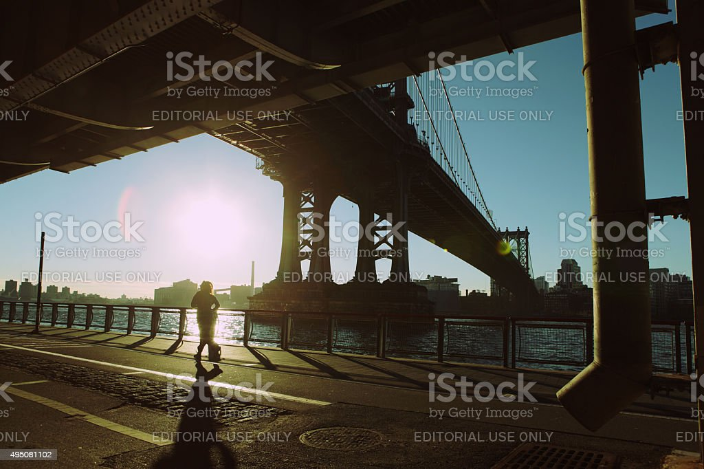 Runner jogs in the sunrise under the Manhattan Bridge NYC stock photo