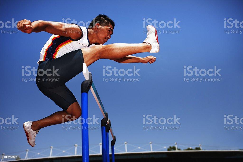 Runner jumping hurdles on track stock photo