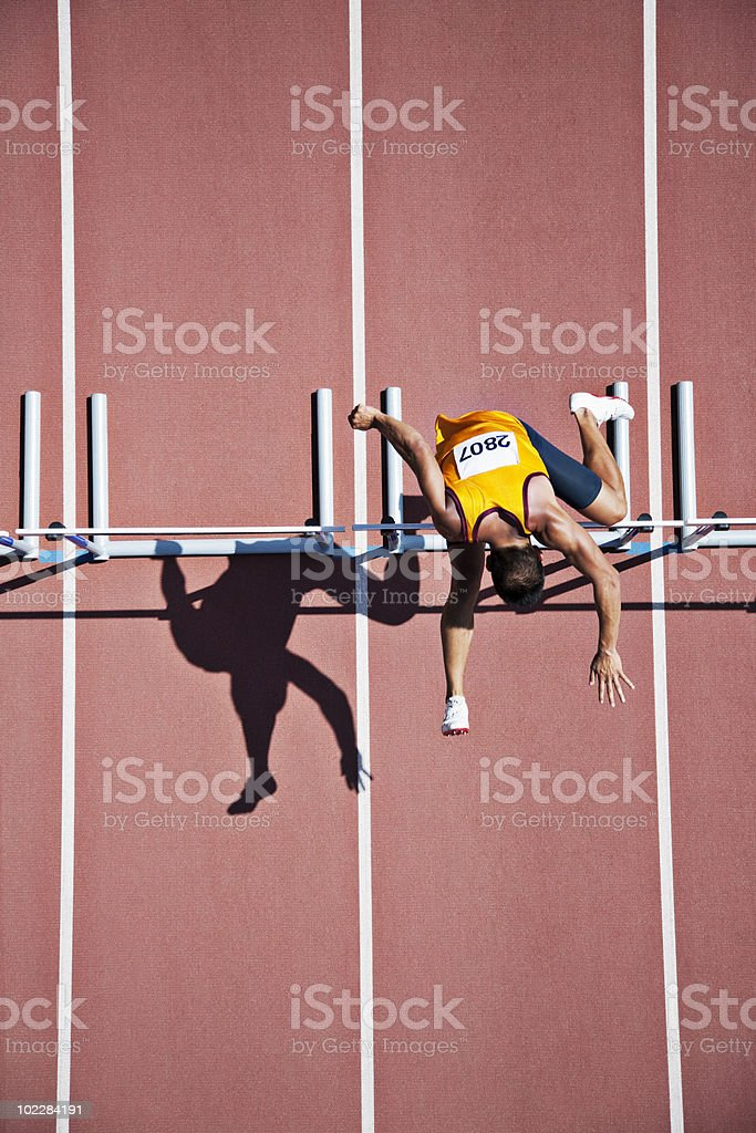 Runner jumping hurdles on track stock photo