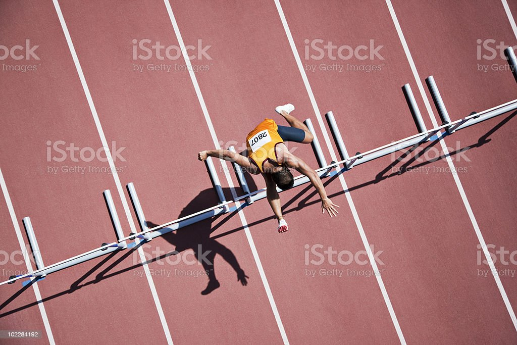 Runner jumping hurdles on track royalty-free stock photo