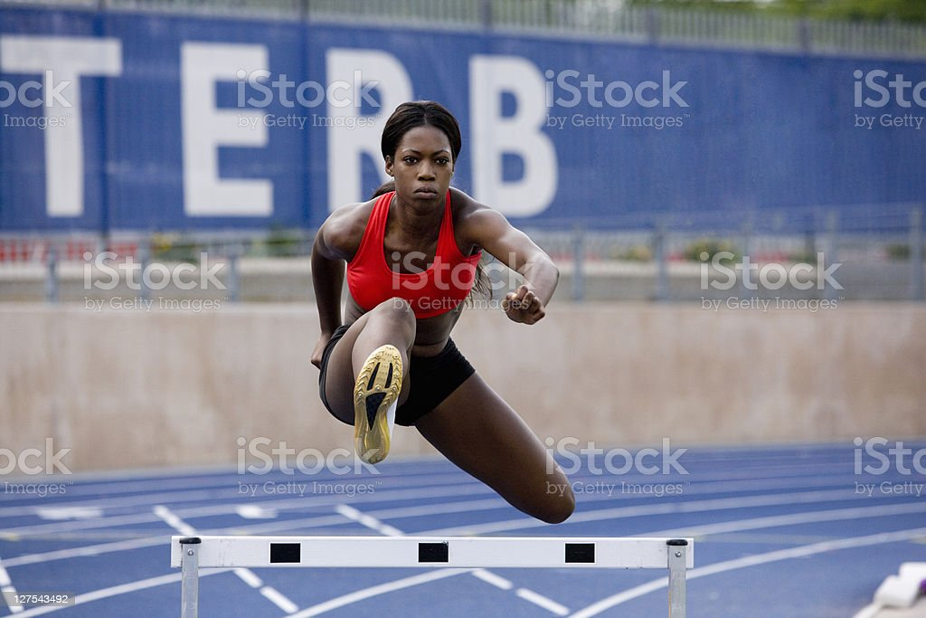 Runner jumping over hurdles on track stock photo