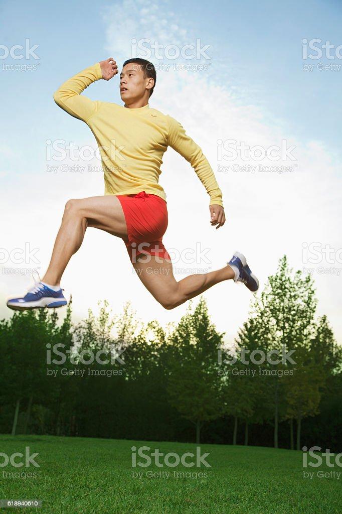 Runner leaping in park stock photo