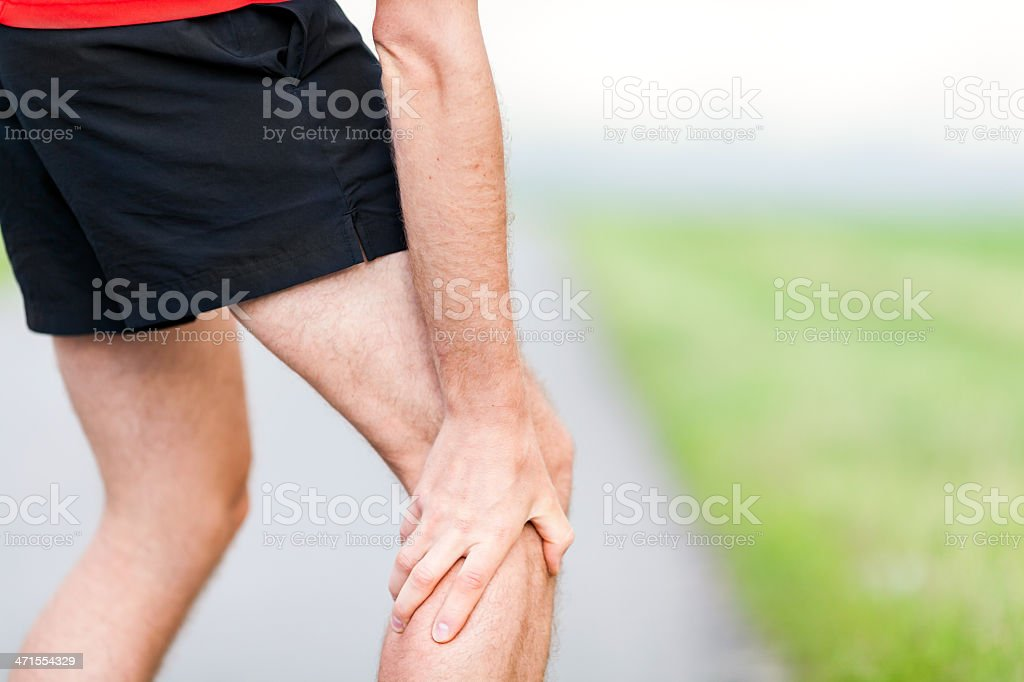 Runner leg and muscle pain during running training outdoors stock photo