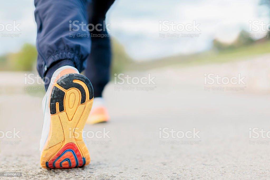Runner Man Feet Running on Road closeup on shoe stock photo