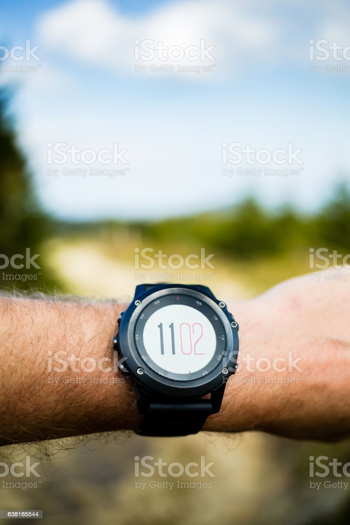 Runner on mountain trail looking at stopwatch, activity tracker stock photo
