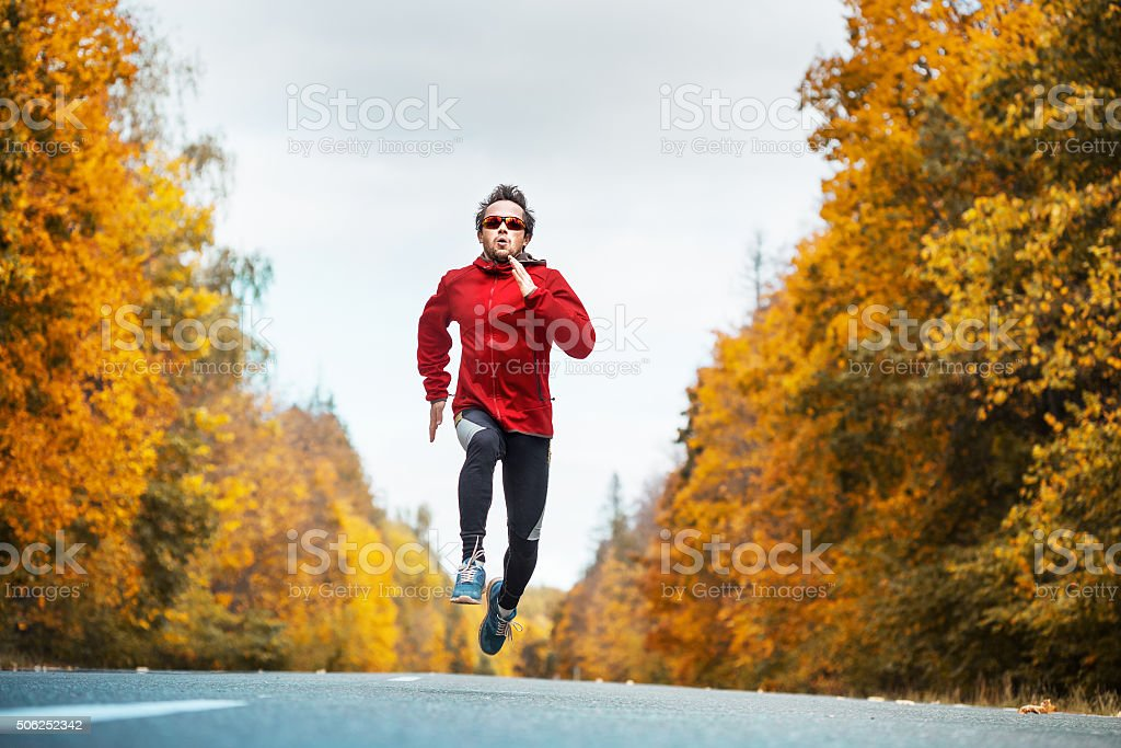 Runner on the autumn road stock photo