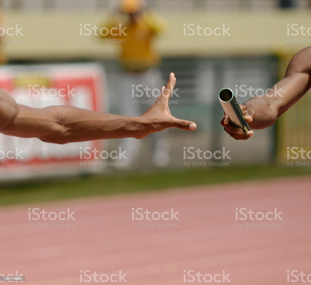 A runner passing a baton to another person stock photo