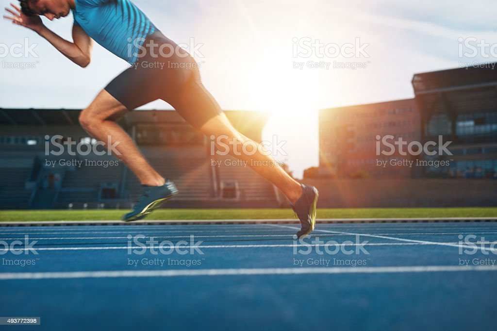 Runner practicing in athletics stadium stock photo