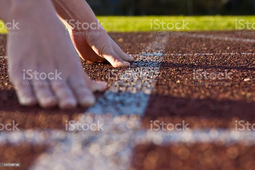 Runner preparing to race with hands on start line stock photo