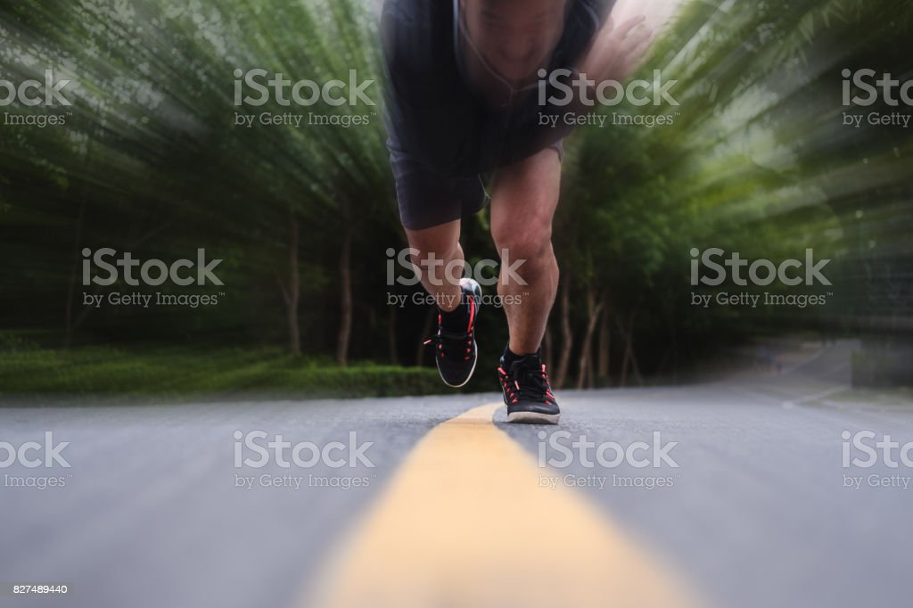 Runner running on the road, selective focus on shoes, with speed...