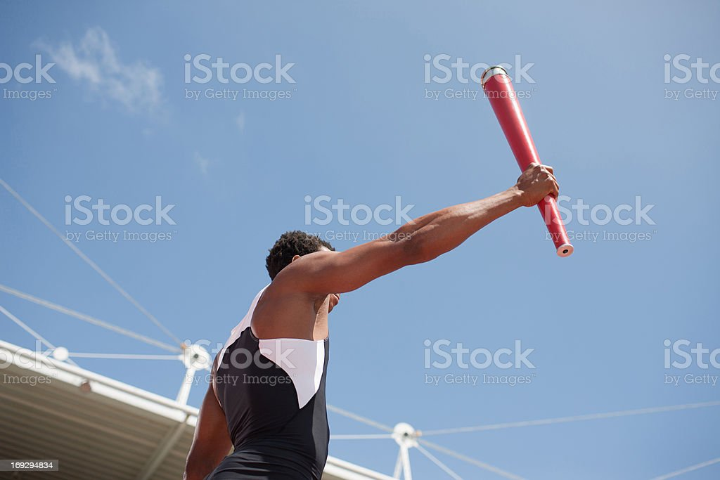 Runner running with torch on track royalty-free stock photo
