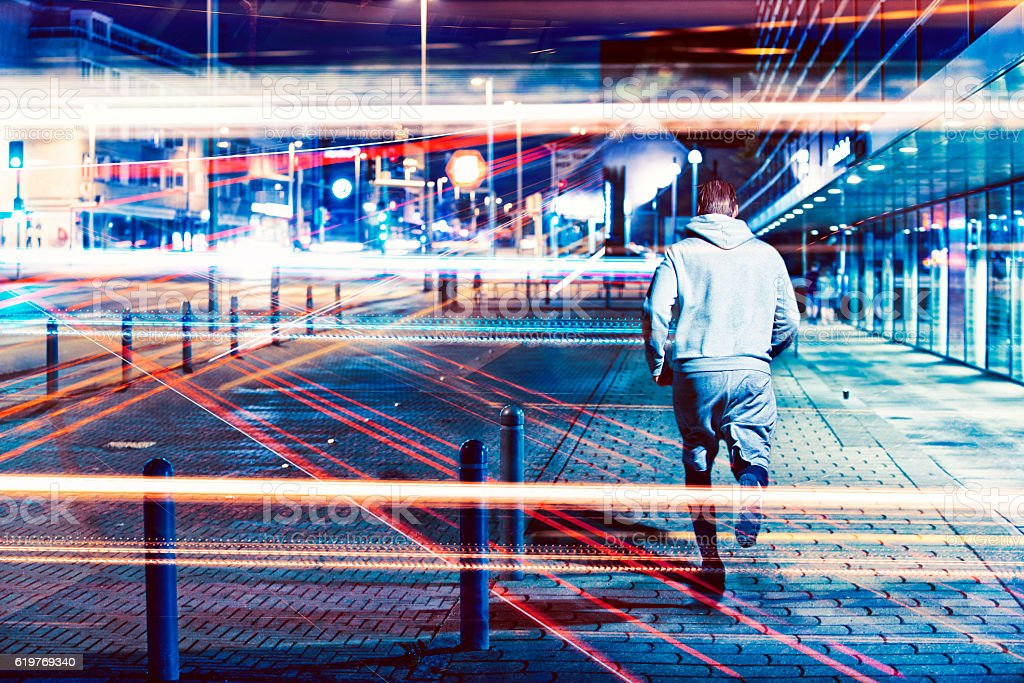 Runner runs through city at night with lots of lights stock photo