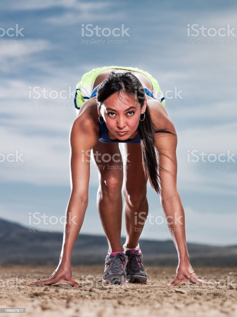 A women in the runner\'s starting position on a dry lake bed.