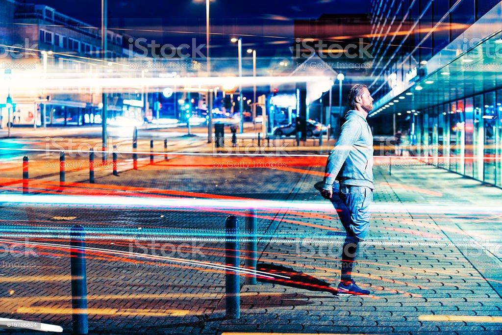 Runner stretches leg before run in city at night stock photo