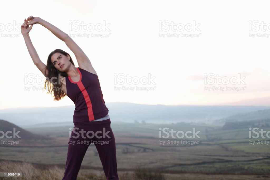 Runner stretching in rural landscape stock photo