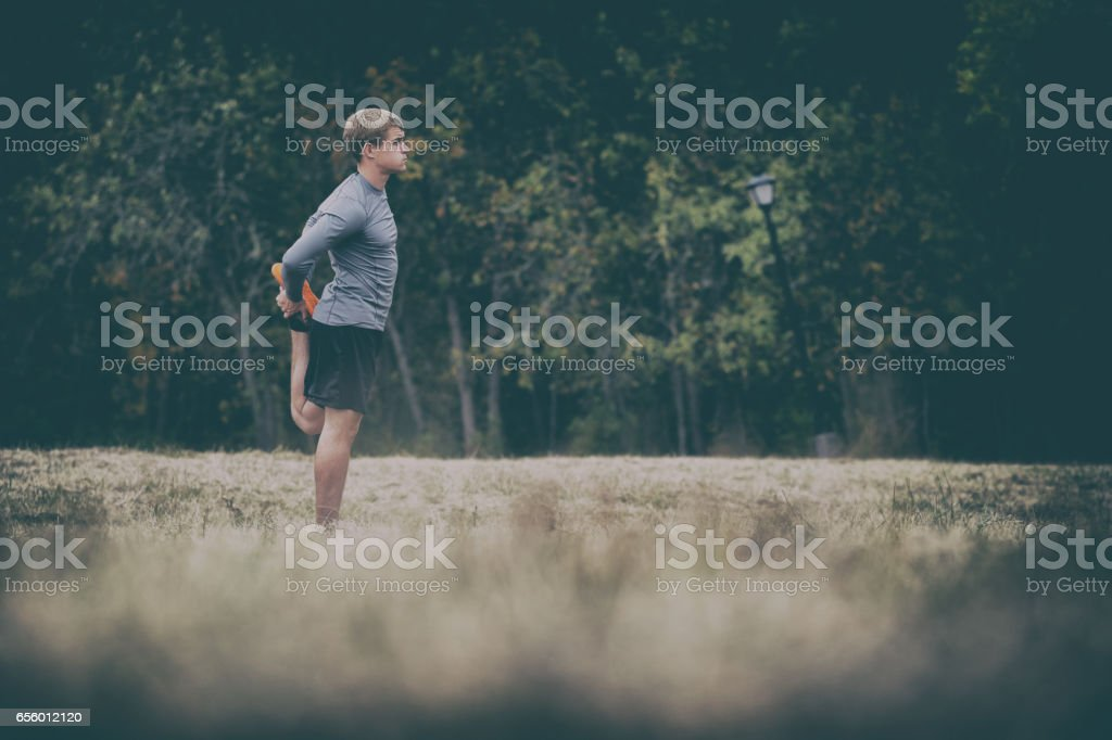 Runner Stretching on Dark Moody Day stock photo
