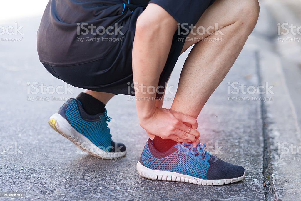 Runner touching painful twisted or broken ankle. Runner training accident stock photo