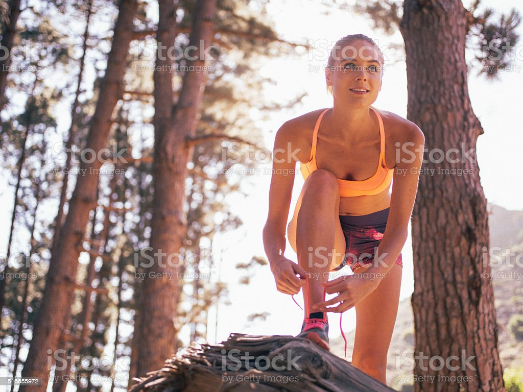 Runner tying her shoelaces and looking at the trail ahead stock photo