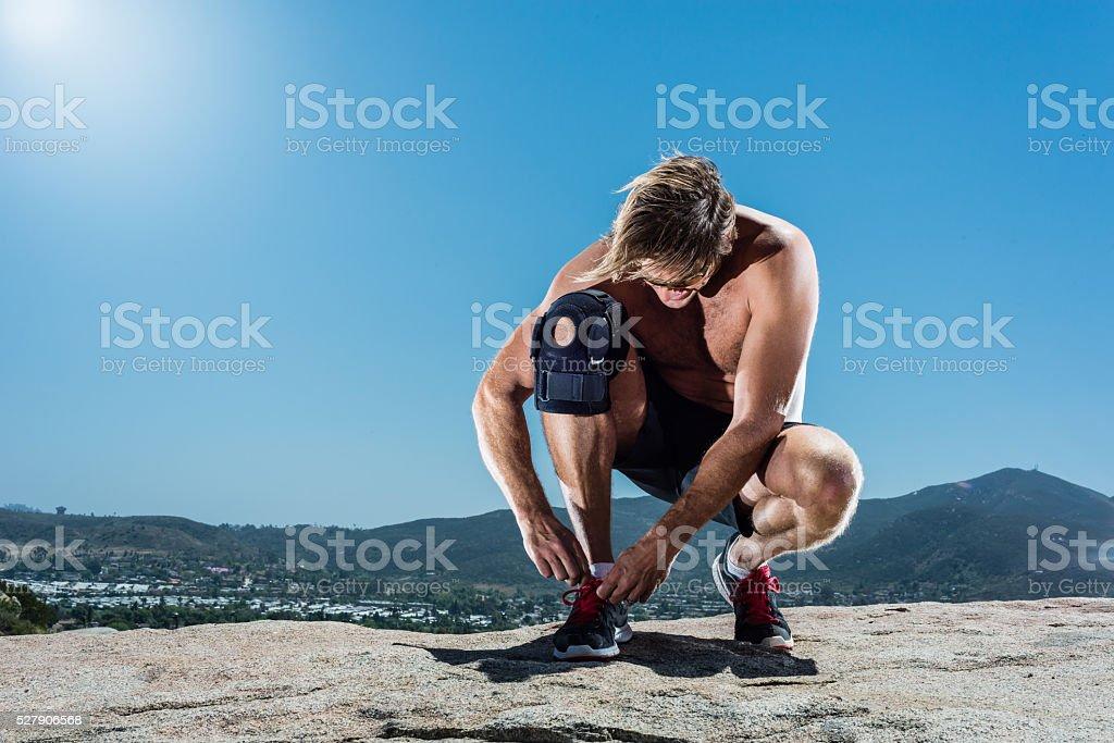 Runner Tying His Shoe With Knee Brace stock photo