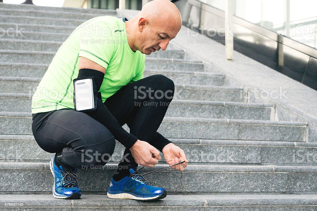 Runner Tying His Shoelaces, Cityscape On Background stock photo