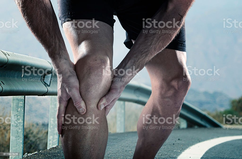 runner with athletic legs holding knee suffering muscle pain stock photo