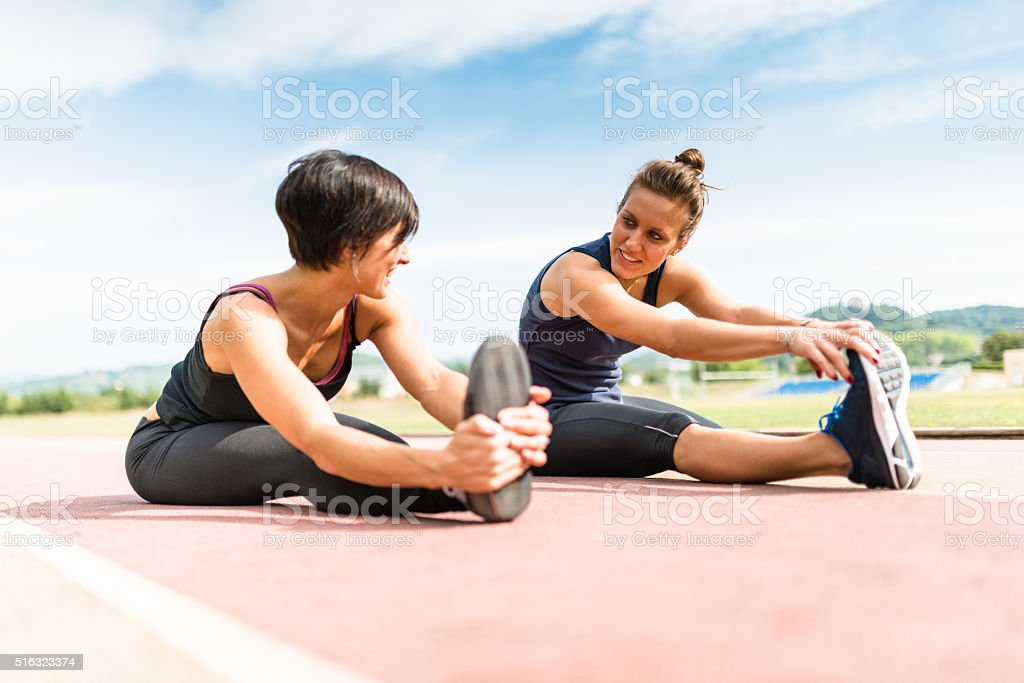 runners doing stretching on the track stock photo