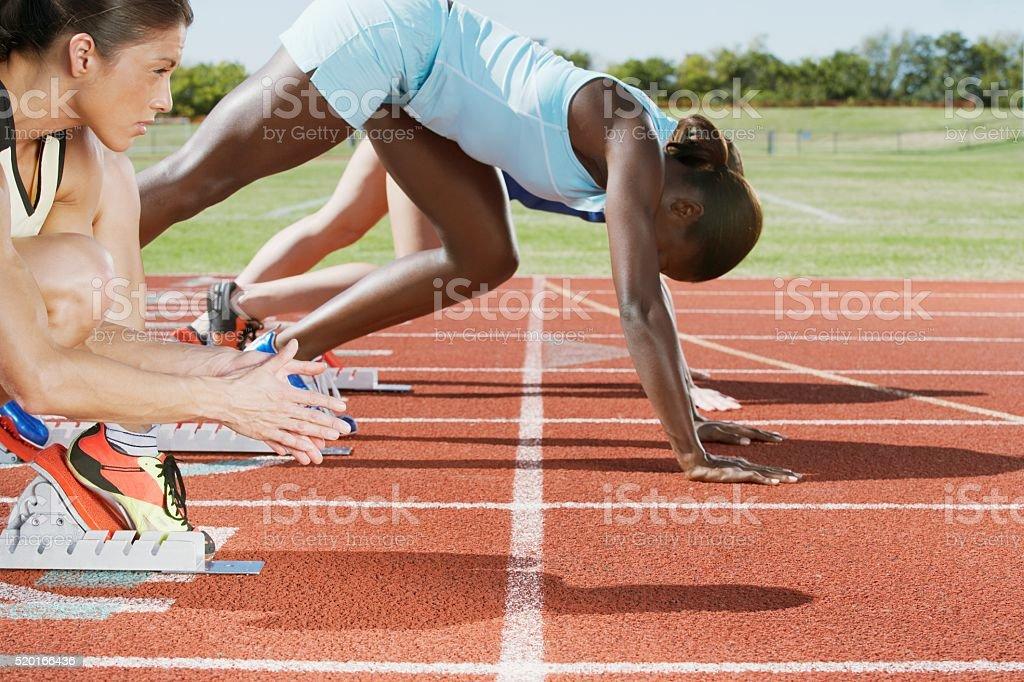 Runners in starting blocks stock photo