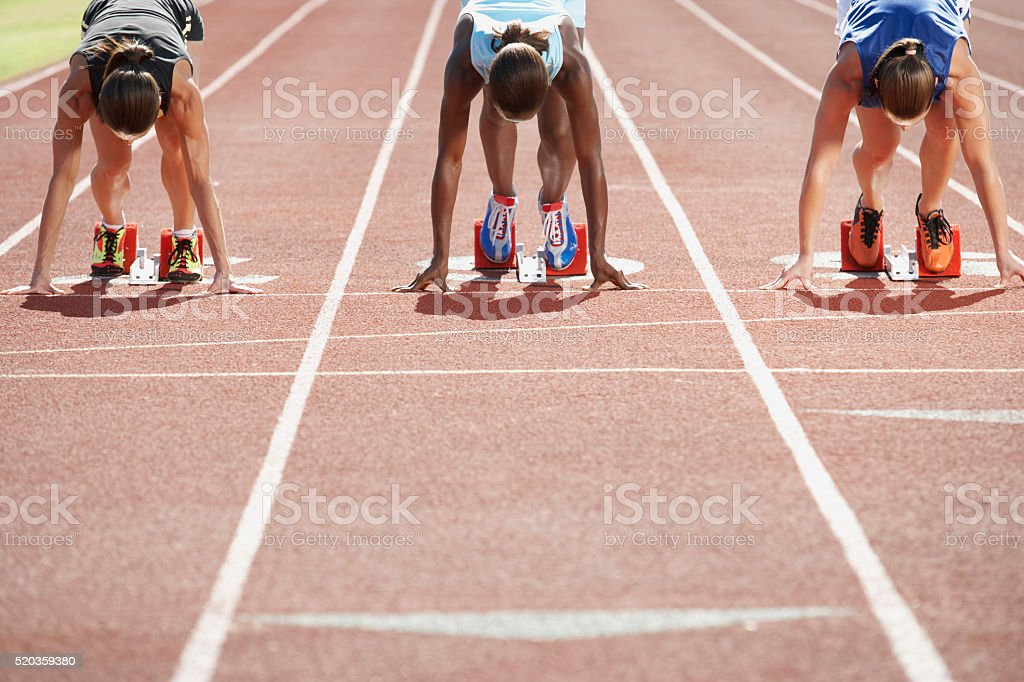 Runners in starting blocks stock photo
