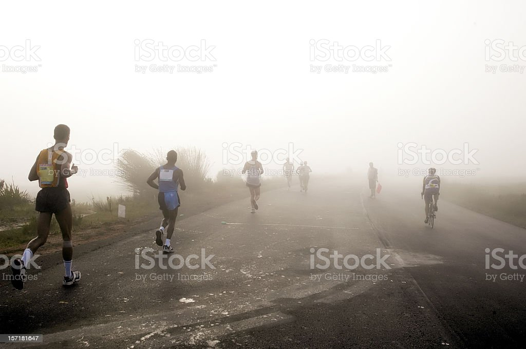 Runners jogging in early morning mist stock photo