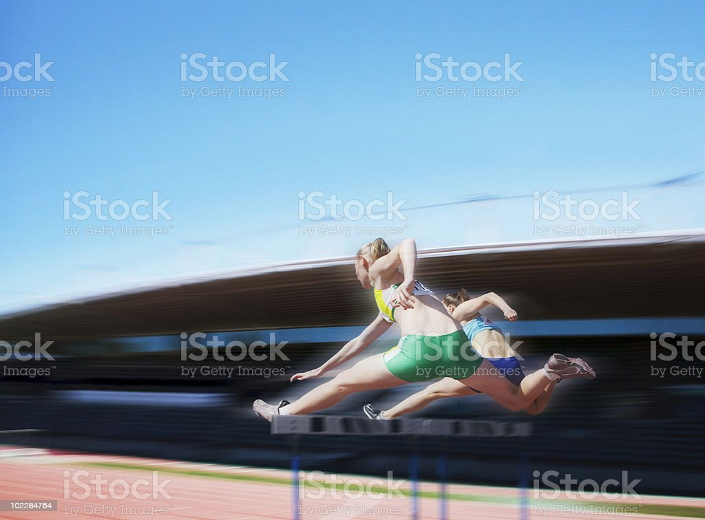Runners jumping over hurdles royalty-free stock photo