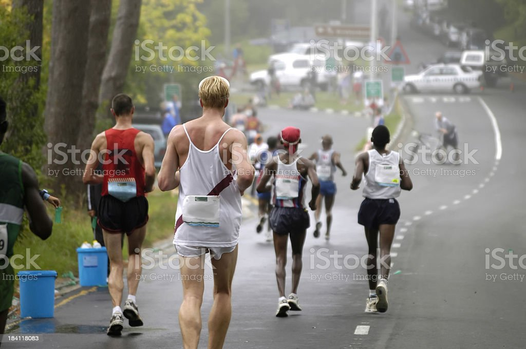 Runners on a downhill road stock photo