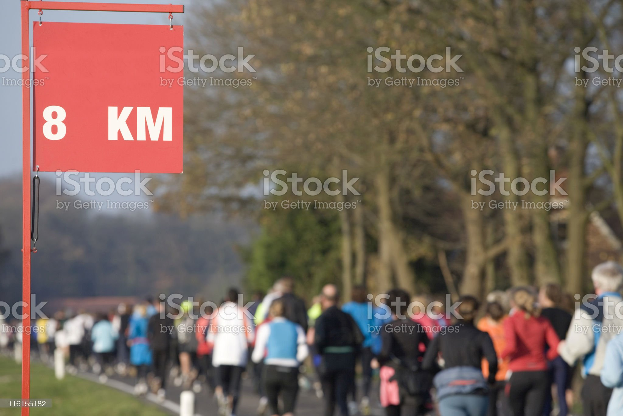 runners passing the 8 kilometer sign royalty-free stock photo
